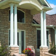 Tall tapered fiberglass columns hold up the high entryway of a residence