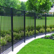 A backyard area is guarded by flat topped metal picket fence