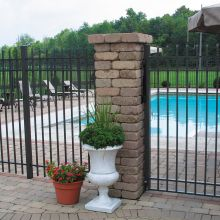 A custom gate attaches to brick pillars to limit access to a residential swimming pool