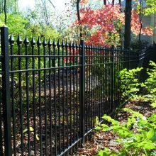 A backyard is guarded by picket railing with decorative picket toppers