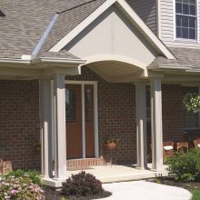 Panel style aluminum columns guide the path to the front porch entrance of a home
