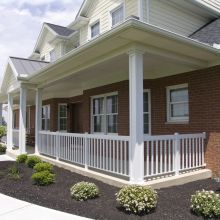 Square panel columns with aluminum railing attached line a front porch