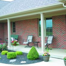 Two panel columns use their load-bearing strength to hold up a front porch overhang