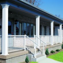 Smooth columns with decorative caps combine with railing to line the entryway of a small town Ohio business