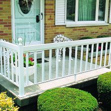 Porch railing attaches to square porch columns to border a residential front porch