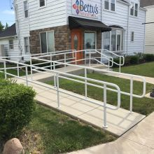 Ramp pipe railing and step pipe railing installed to assist customers trying to enter a natural food store