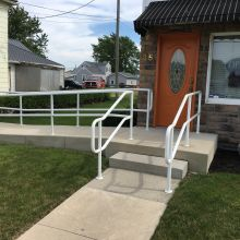 Pipe railing is setup to assist customers in traversing the stairs at a natural food store