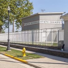 A high school baseball field has controlled access because of aluminum fence