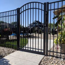 A custom arched gate closes off access to a residential swimming pool