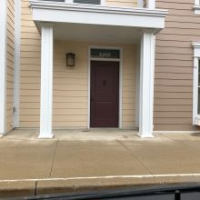An Ohio apartment entrance featuring a small overhang supported by square panel columns