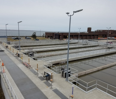 Pipe railing surrounds multiple tanks at a wastewater treatment plant in New York