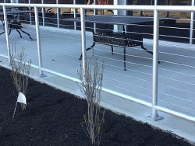 Pipe cable railing on the outdoor dining patio of an industrial business providing an unimpeded view to the street