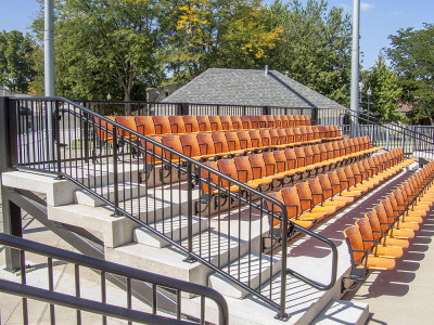 Pipe picket railing with pipe handrail is situated to help patrons reach their seats at a high school baseball field
