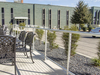 A manufacturing facilities outdoor patio is enclosed by pipe cable railing