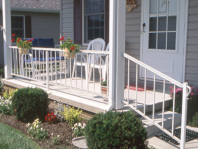 Porch railing safeguards the front of a small elevated entryway