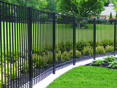 Metal picket fence borders the backyard of a residential home