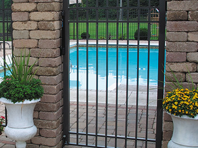 A gate anchored to two brick pillars guards a residential swimming pool
