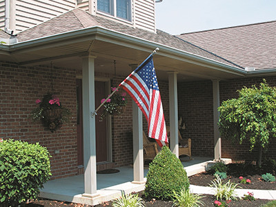 Square fluted porch columns support the overhang of a residential home