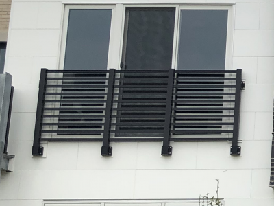 A large apartment window features a juliet horizontal railing with a modern design